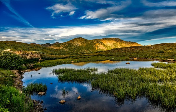 Picture the sky, grass, clouds, mountains, pond