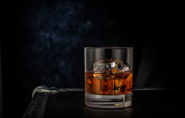 Picture glass, ice, whiskey, the dark background