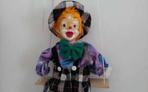 Picture doll, clown, on the swings