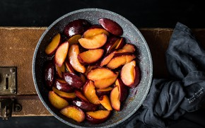 Picture the dark background, fabric, suitcase, peaches, slices, pan, chopped