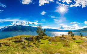 Picture the sky, grass, the sun, clouds, rays, trees, mountains, stones, shore, Bay, Iceland