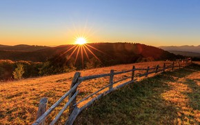 Picture the sky, grass, the sun, rays, trees, mountains, dawn, the fence, field, meadow, forest