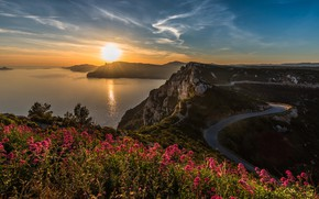 Picture road, sea, summer, the sun, clouds, rays, light, sunset, flowers, mountains, glare, blue, stones, rocks, …