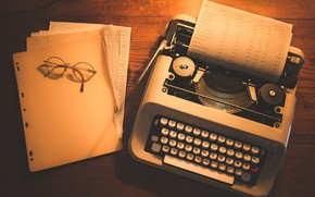 Picture glasses, typewriter, wooden table, leaves, documents