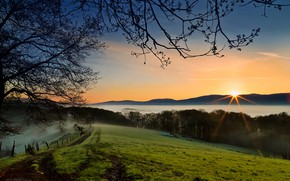 Picture the sky, grass, the sun, rays, trees, mountains, branches, fog, the fence, slope, meadow, path