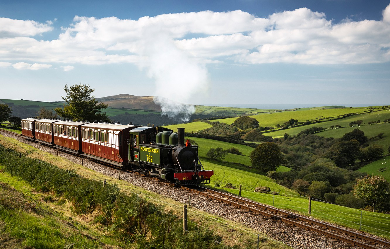 Photo wallpaper the sky, the sun, clouds, trees, hills, field, England, rails, train, the engine, cars, railroad, ...