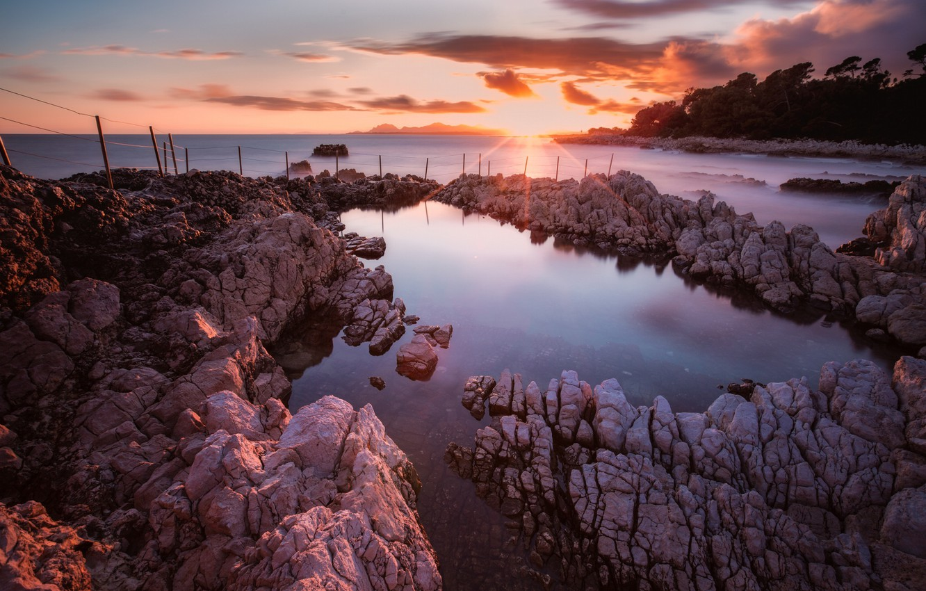 Photo wallpaper the sky, the sun, clouds, rays, light, trees, sunset, stones, rocks, shore, posts, the evening, …