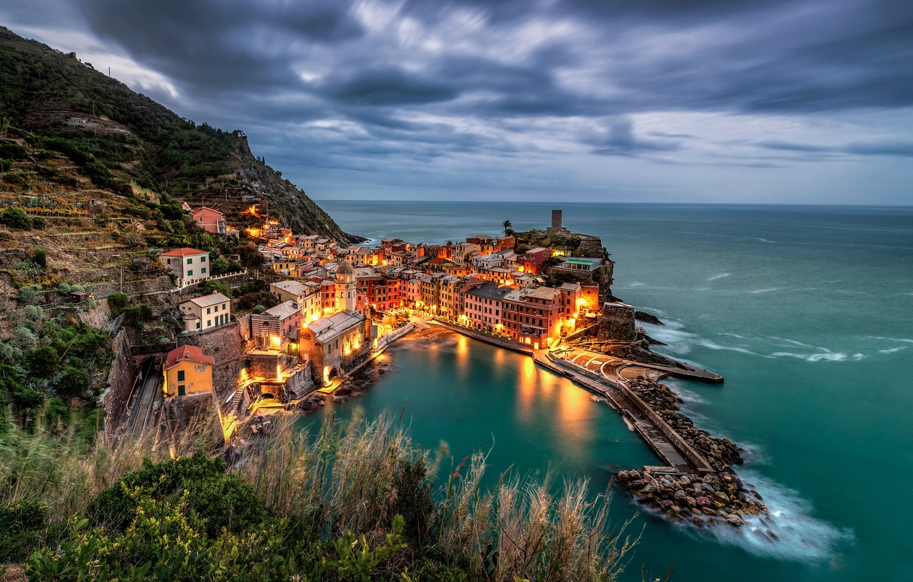 Photo wallpaper sea, grass, clouds, the city, lights, view, building, home, the evening, slope, horizon, Italy, twilight, …