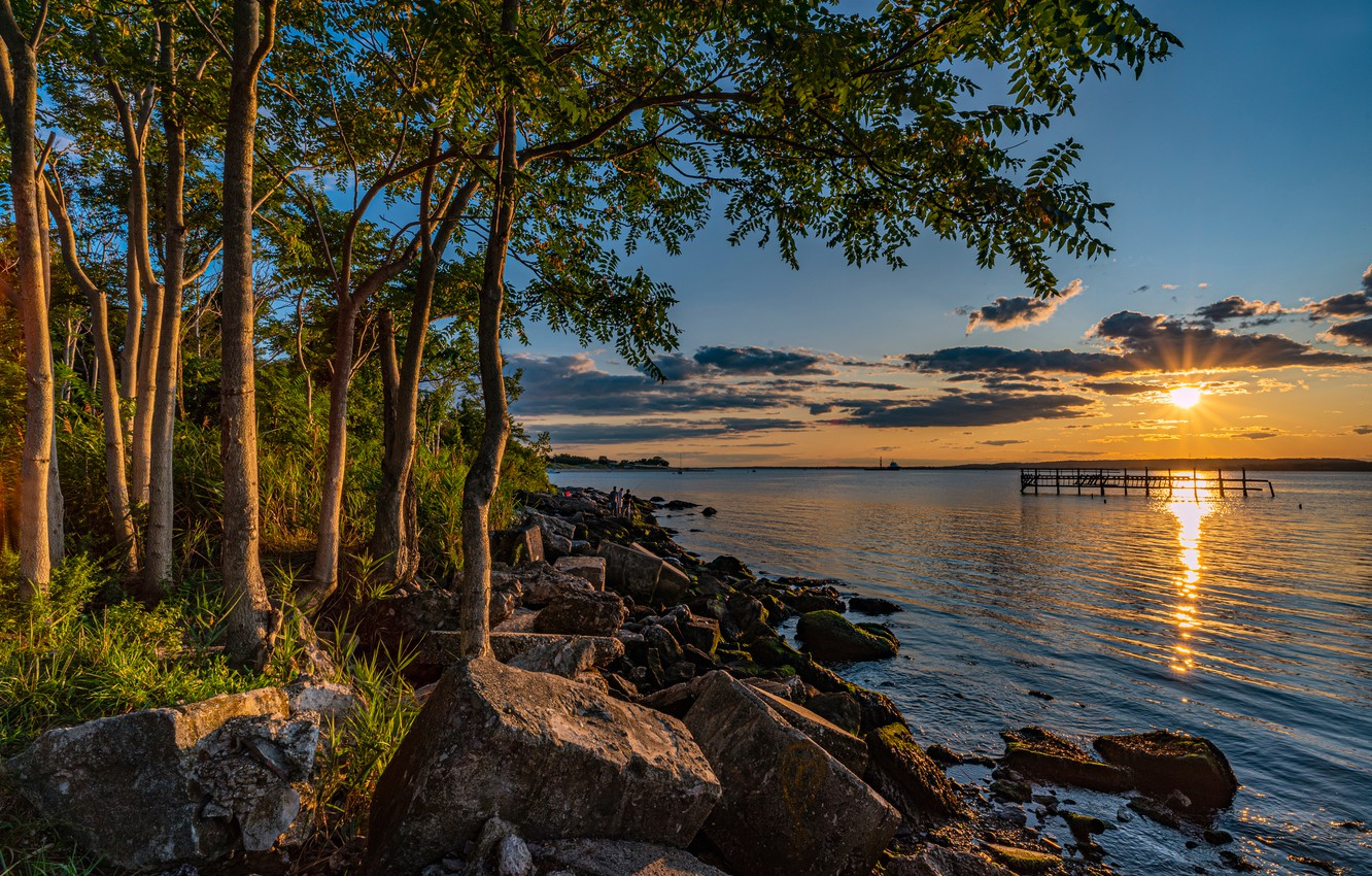 Photo wallpaper the sky, the sun, clouds, trees, sunset, stones, shore, Bay, USA, Brooklyn