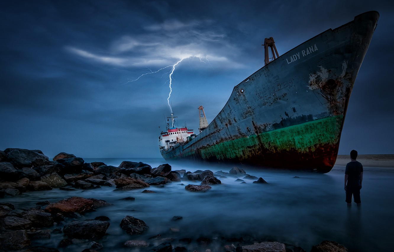 Photo wallpaper sea, stones, lightning, people, ship, stranded