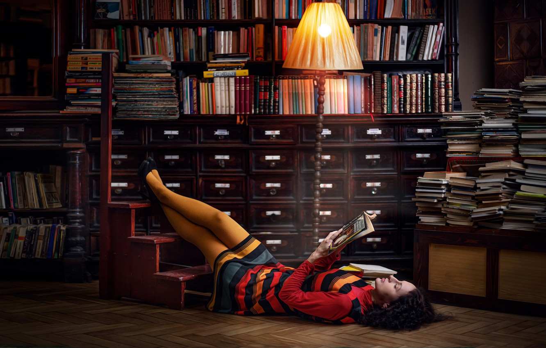 Photo wallpaper pose, model, books, lamp, makeup, dress, brunette, hairstyle, shoes, lies, library, legs, twilight, floor lamp, …